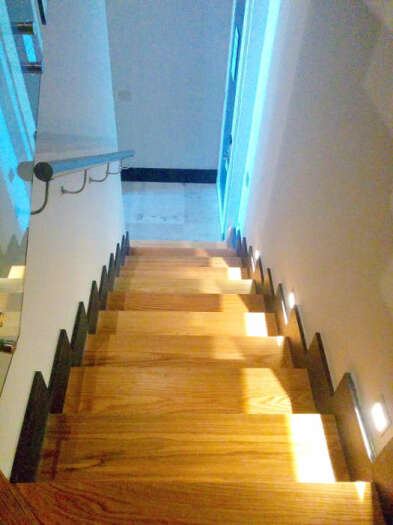 The stairs are well lit and have railings.  This photo shows the good lighting that accents the stairwell.