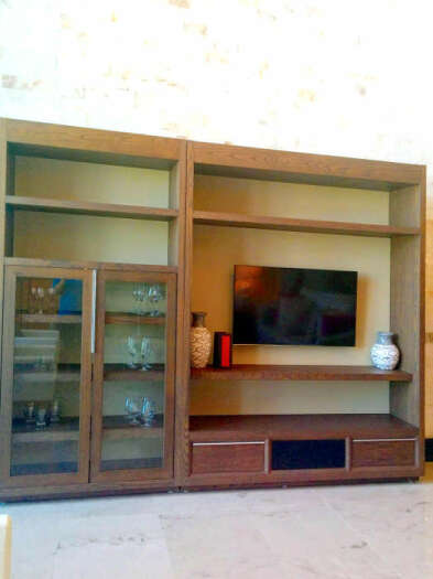The wall unit in the living area contains a flatscreen TV and additional storage space.